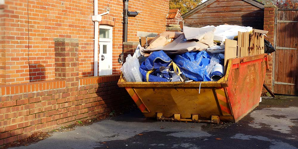 skip on driveway filled with waste