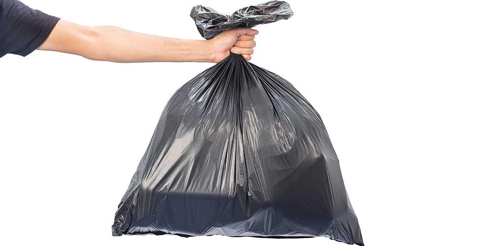 Man Holding a Rubbish Bag